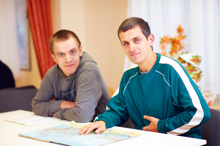 Cheerful adult men with disability sitting