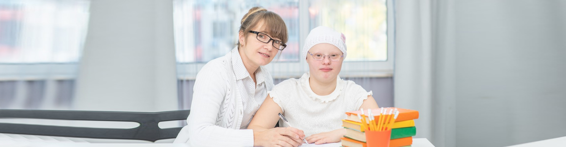 woman assisting young girl in writing